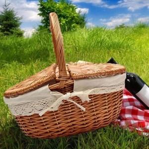 Panier de pique-nique en osier en osier comme sac à provisions avec couvercle et poignée et doublure blanche pour le pique-nique en camping en plein air portant des aliments